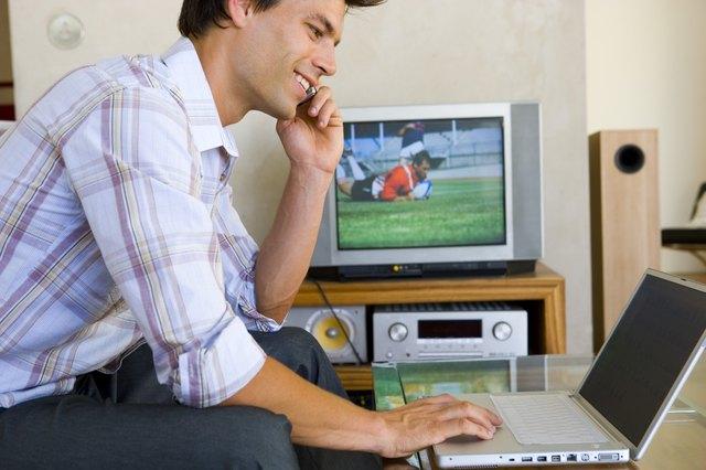 Man using cellular phone while on laptop