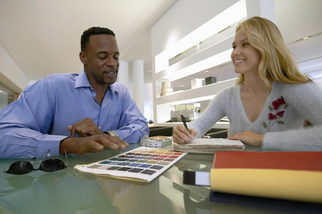 Man Sits at a Table in an Interior Design Shop Discussing a Colour Chart With a Female Shop Assistant