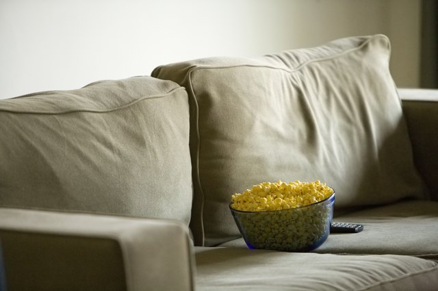 Bowl of popcorn and remote control on sofa
