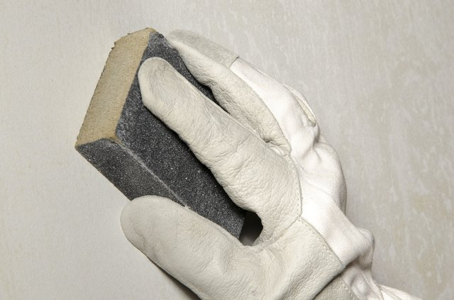 Hand sanding the wall with a sanding sponge
