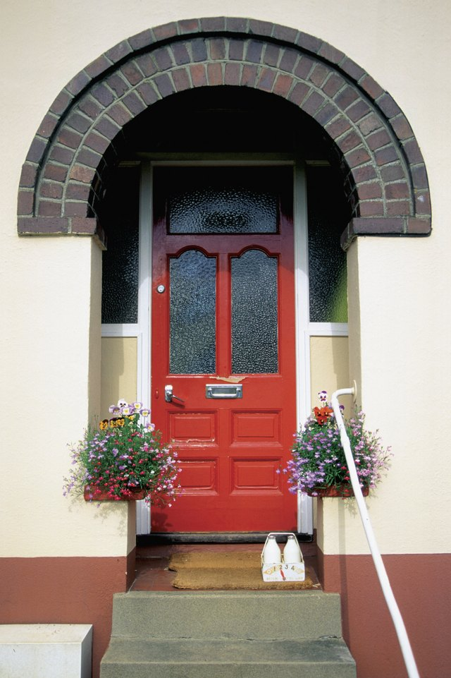 Bottles of milk and hanging plants outside house with red door in Totnes, England