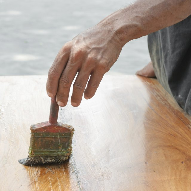 Varnishing antique wooden table  using paintbrush