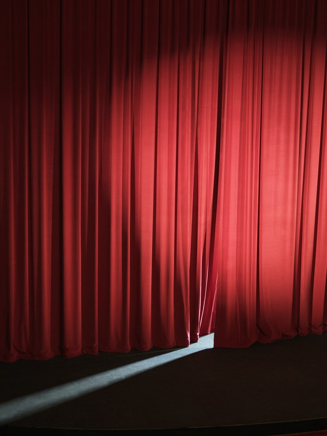 Empty stage with curtains slightly open letting light through