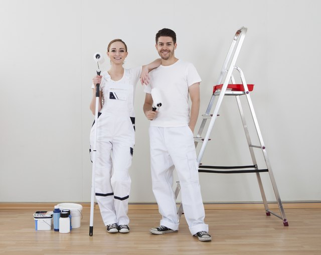 Young Couple Holding Paint Roller