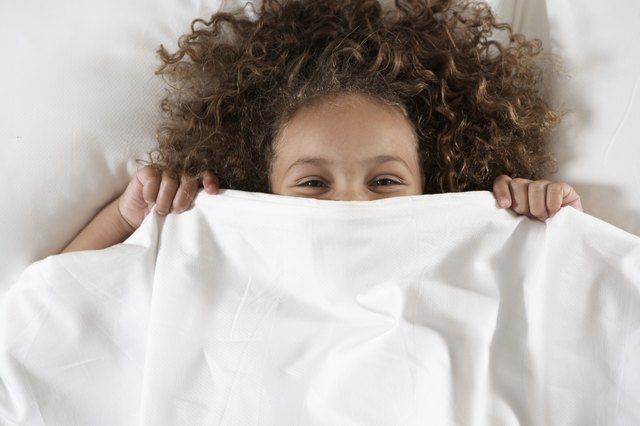 Girl (5-7) covering face with sheet in bed, portrait, overhead view