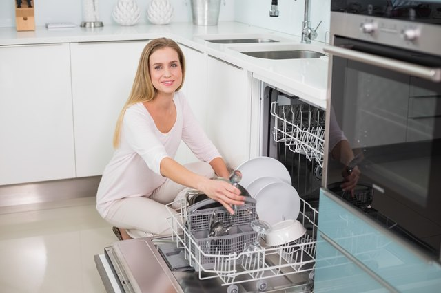 Smiling gorgeous model kneeling behind dish washer