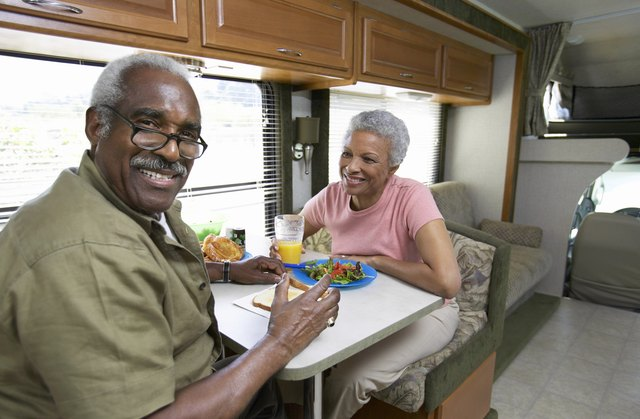 Senior Couple Sit at a Table in a Motor Home, Having Lunch