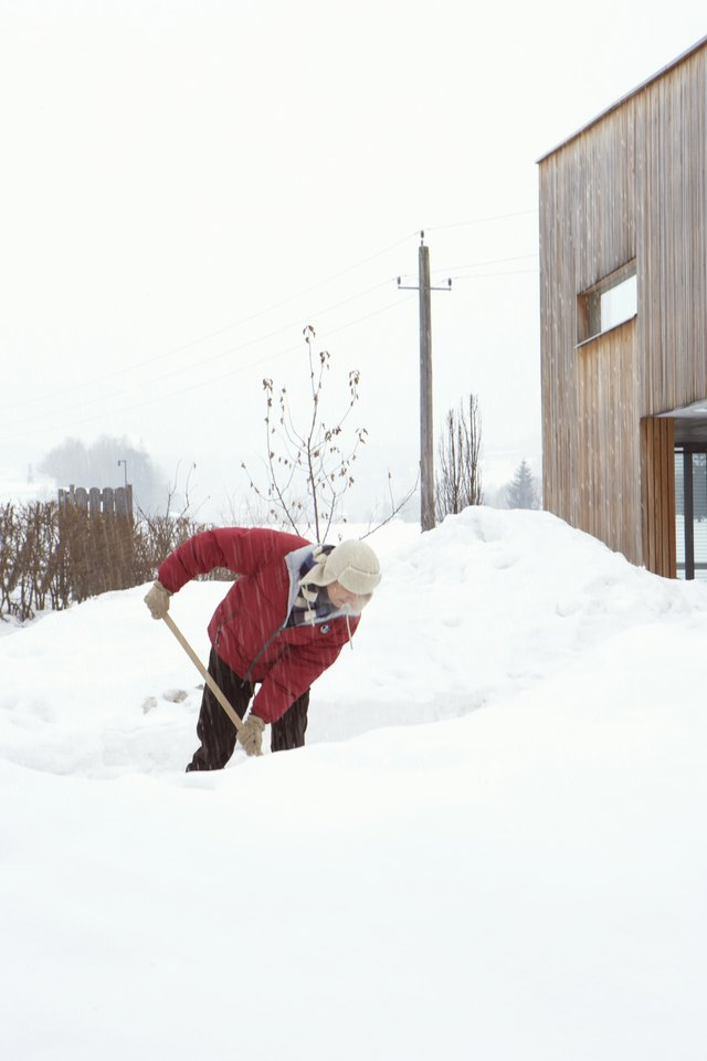 Man wearing hat shovelling deep snow on driveway