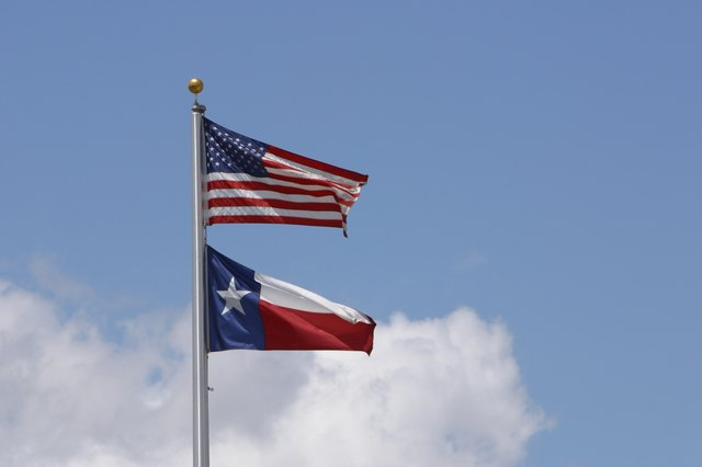 American flag and state flag of Texas in sky