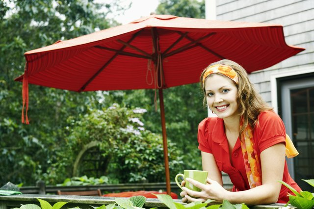 Smiling woman with coffee by patio umbrella