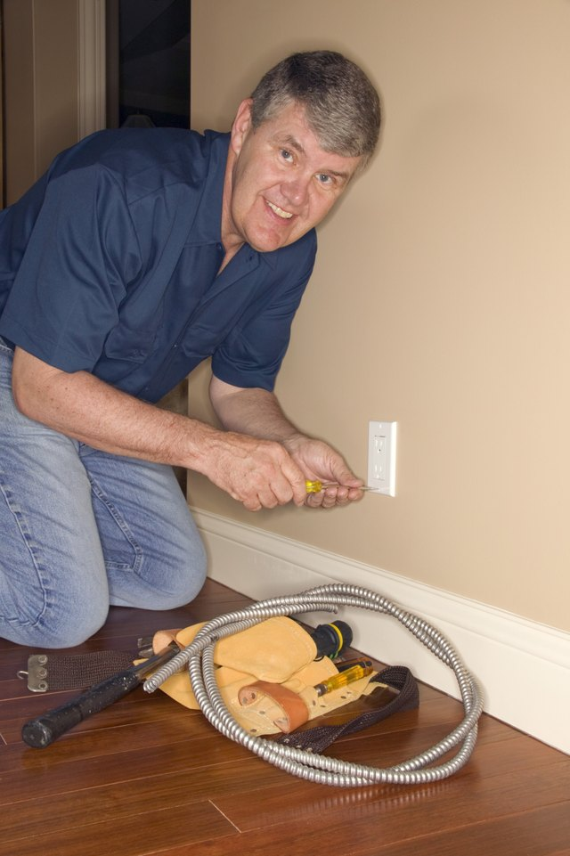Man working on electrical outlet