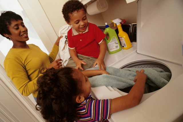 Mother with son and daughter (4-5) putting laundry into washing machine
