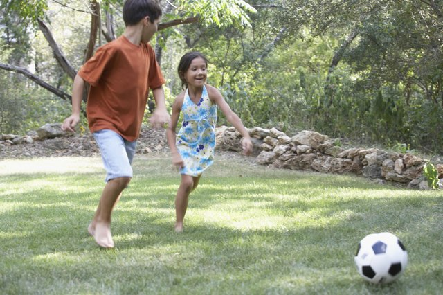 Front profile of a boy and a girl playing football in a garden