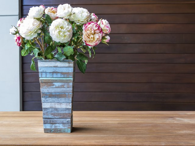 Artificial flowers with rustic wooden vase in modern interior room