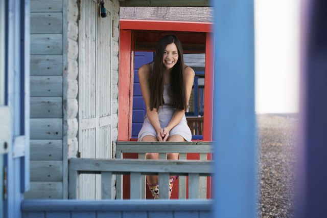 Woman sitting on balustrade of beach house, portrait