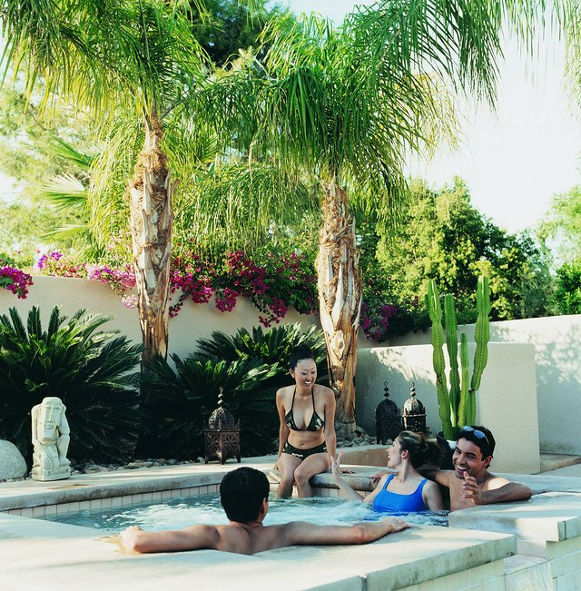 Two Couples Enjoying a Hot Tub in a Hotel's Courtyard