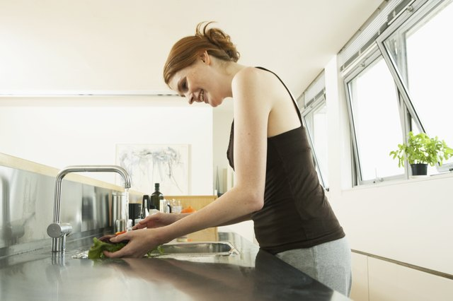Young woman washing lettuce at kitchen sink, smiling, side view