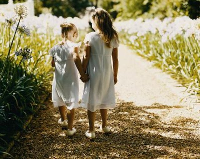 Rear View of Two Bridesmaids Walking Down a Gravel Path Between Flowerbeds