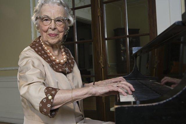 Senior woman playing piano, smiling, portrait