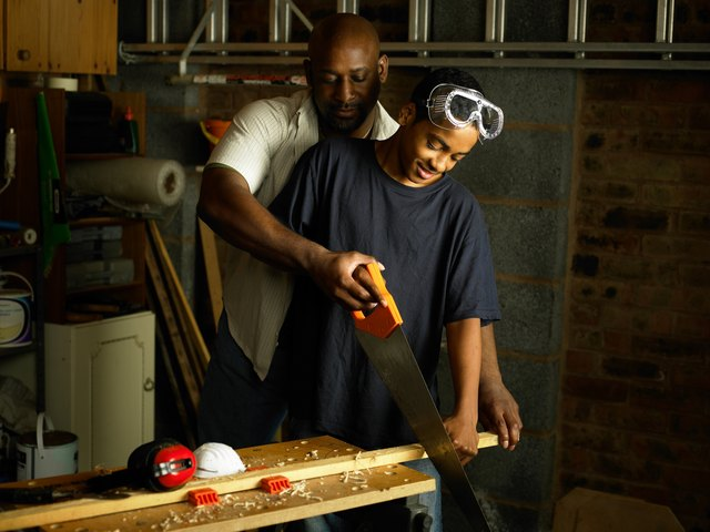 Father helping teenage Son with woodwork