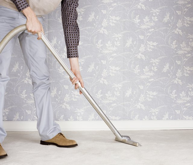 Low Section of a Man Using a Vacuum Cleaner