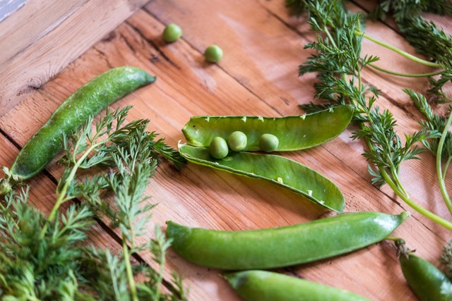 green snow peas in wooden box
