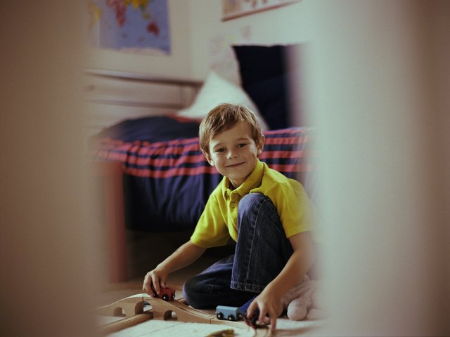 Boy (5-7) playing train sets in bedroom, smiling, portrait