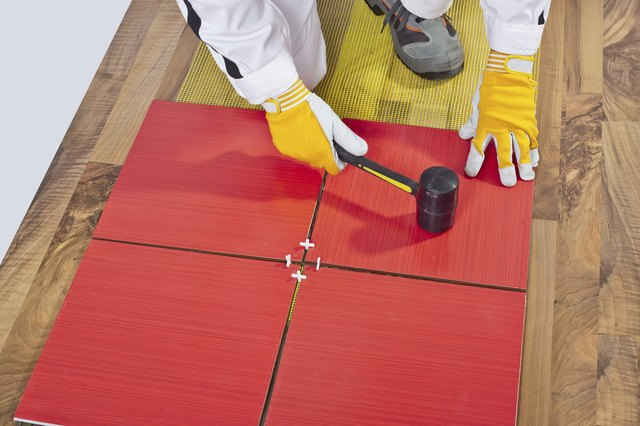 Worker Applies with Rubber Hummer Tile on a wooden Floor