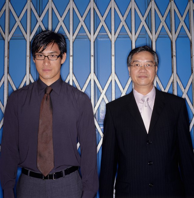 Two businessmen standing in front of sliding metal gate