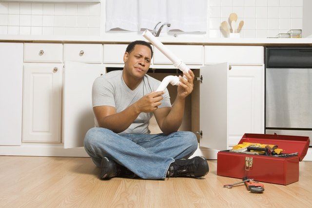 Man sitting on floor with pipe and toolbox