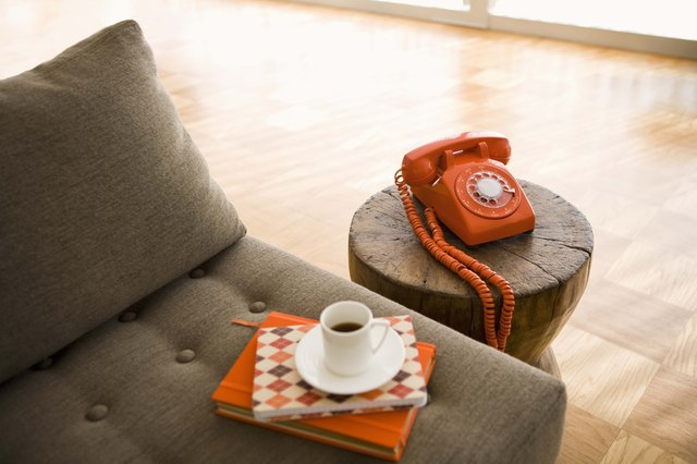 Rotary telephone and cup of coffee on sofa