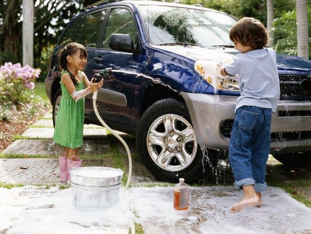Girl (4-6) aiming hose at boy (5-7) washing car on driveway, smiling
