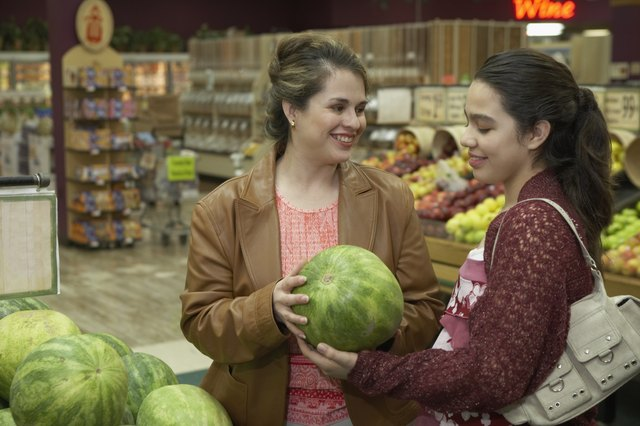 Mid adult woman and her daughter holding a watermelon in a supermarket
