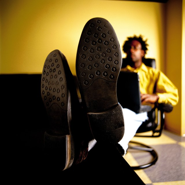 Close-up of shoe soles, man with feet up