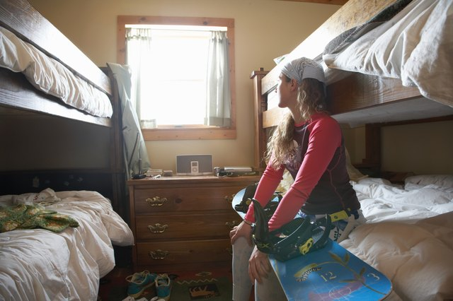 Young woman on bunk bed with snowboard looking out window