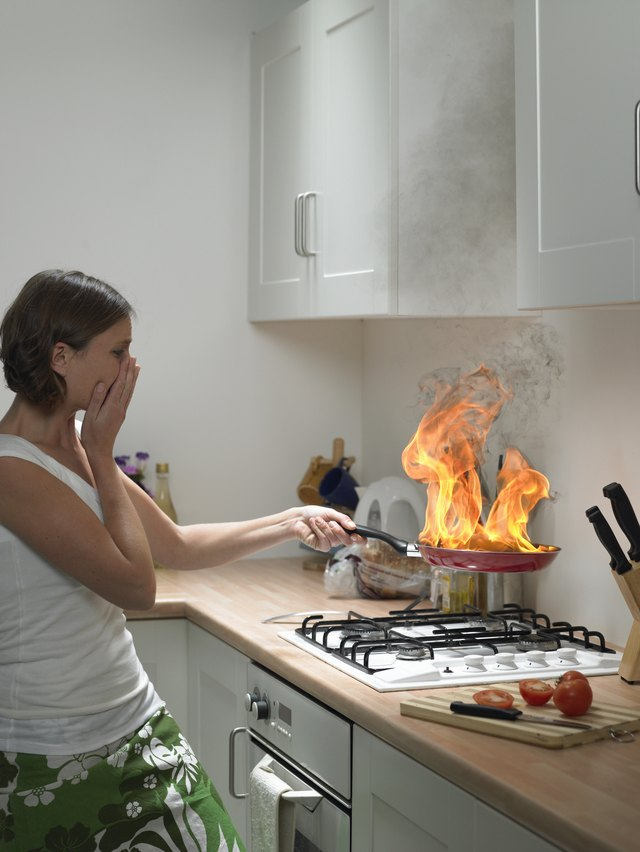 """Woman with hand to face holding burning frying pan in domestic kitchen, side view"""