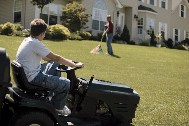 Boy on tractor mower with father raking lawn