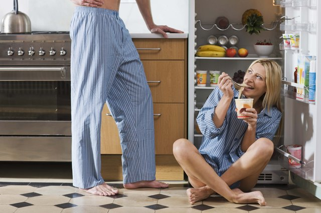 Woman with food sitting by open refrigerator