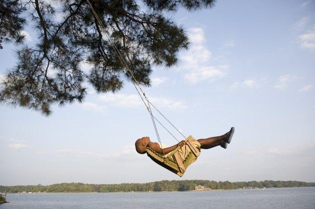 Boy relaxing in swing by lake