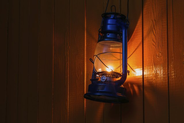 old kerosene lantern hanging on the yellow wooden wall