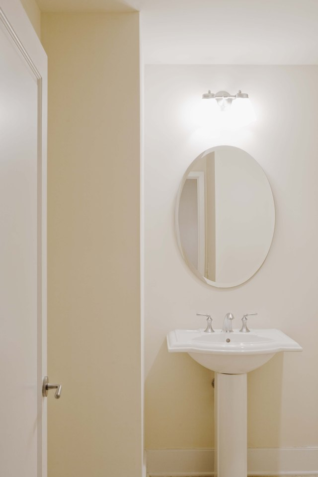 Pedestal Sink And Mirror In Bathroom