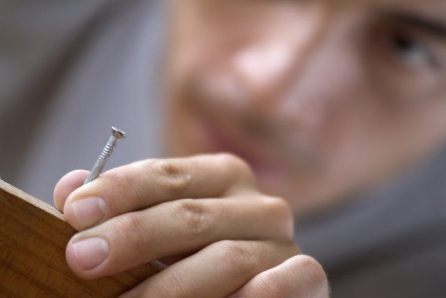 A Young man holding a nail in wood