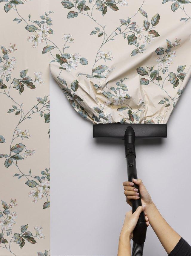 Woman vacuuming wallpaper from wall, close-up