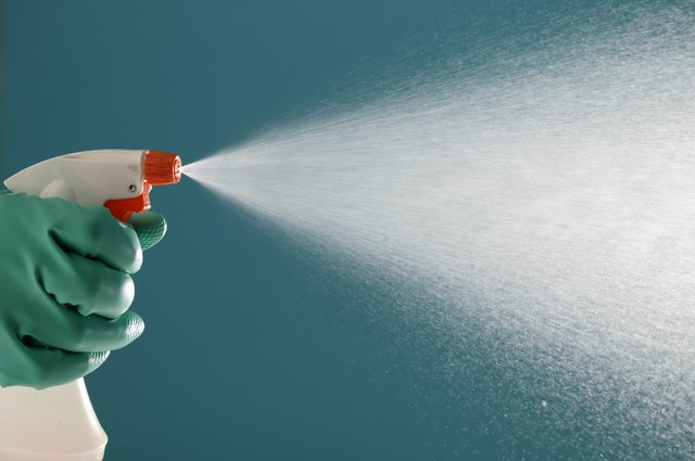 Gloved hand squeezing spray bottle