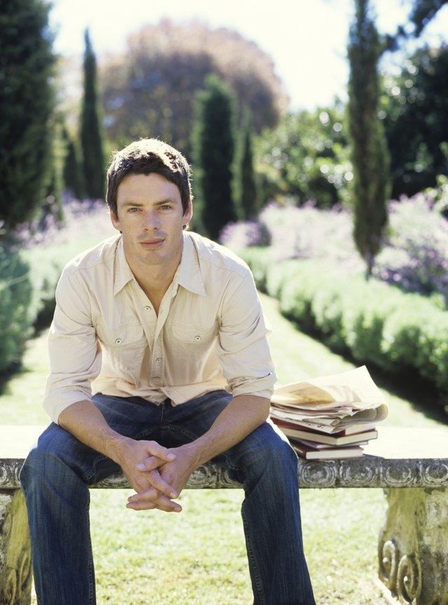 Man sitting on bench in garden, portrait