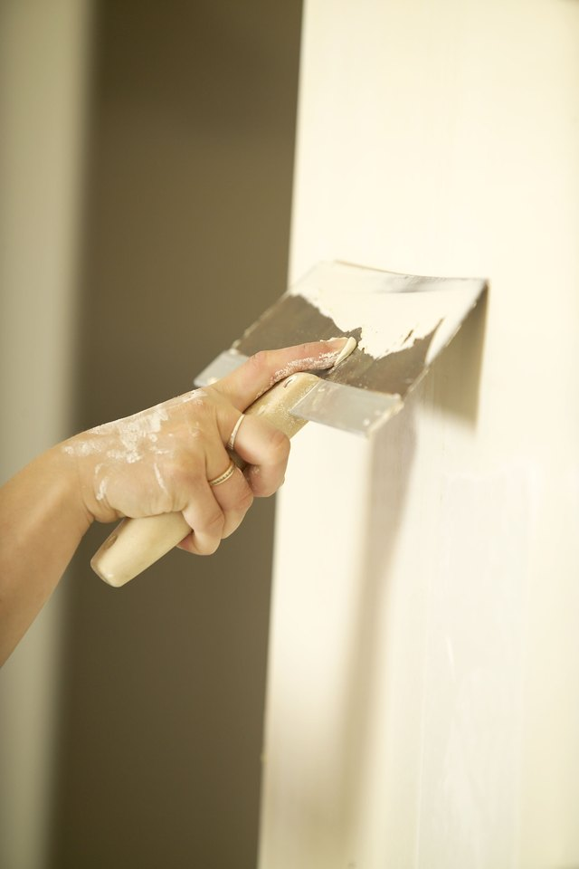 Hand applying plaster to wall