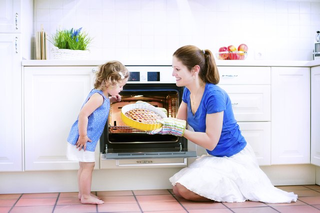 Mother and baby daughter cooking a pie