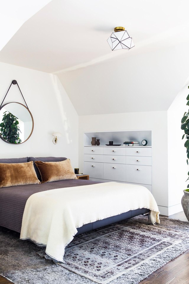 Midcentury bedroom with brown velvet throw pillows and circular mirror above the bed