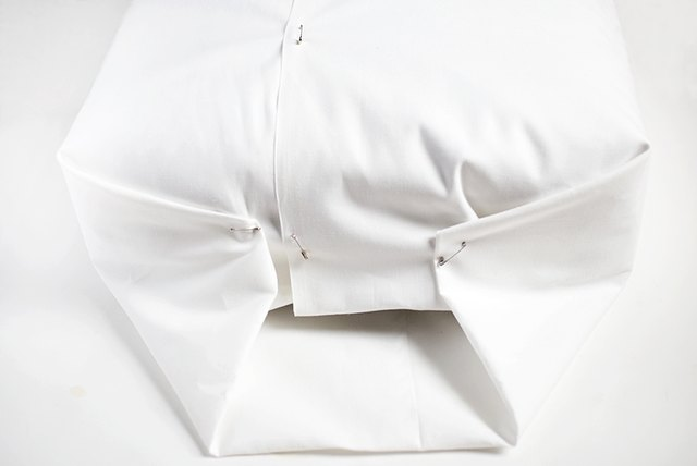 White fabric, safety pinned together over cushions.