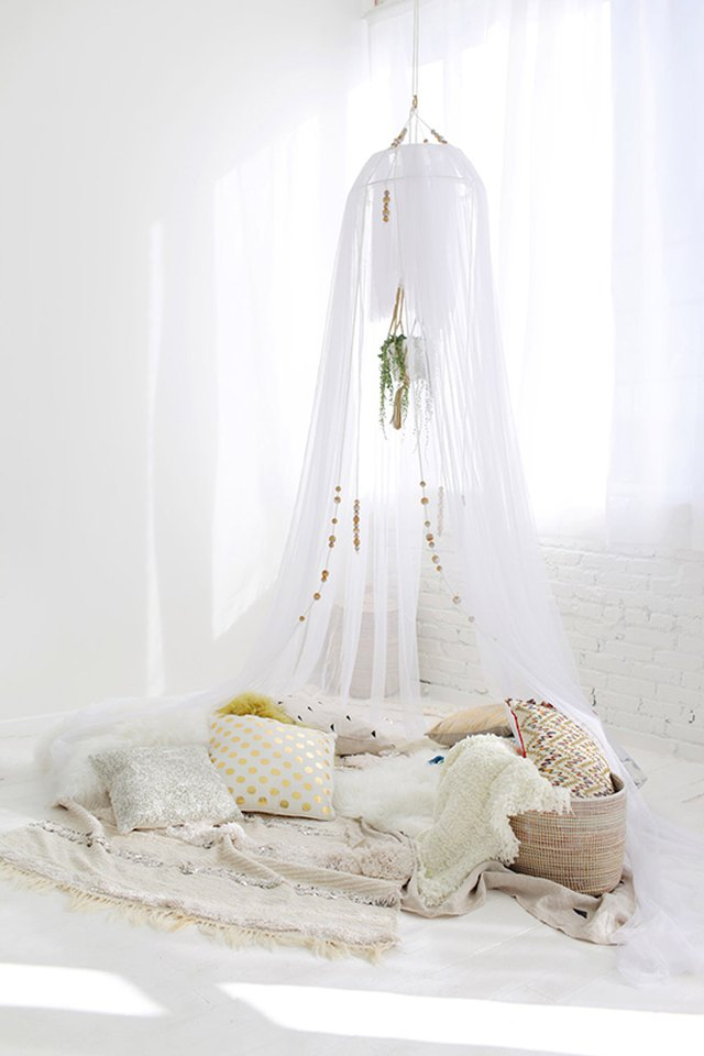 White gauzy fabric hangs from the ceiling and pools around a pillows